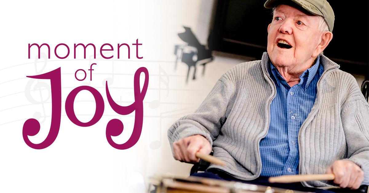 MHA care home resident Tommy in music therapy session with Moment of Joy branding