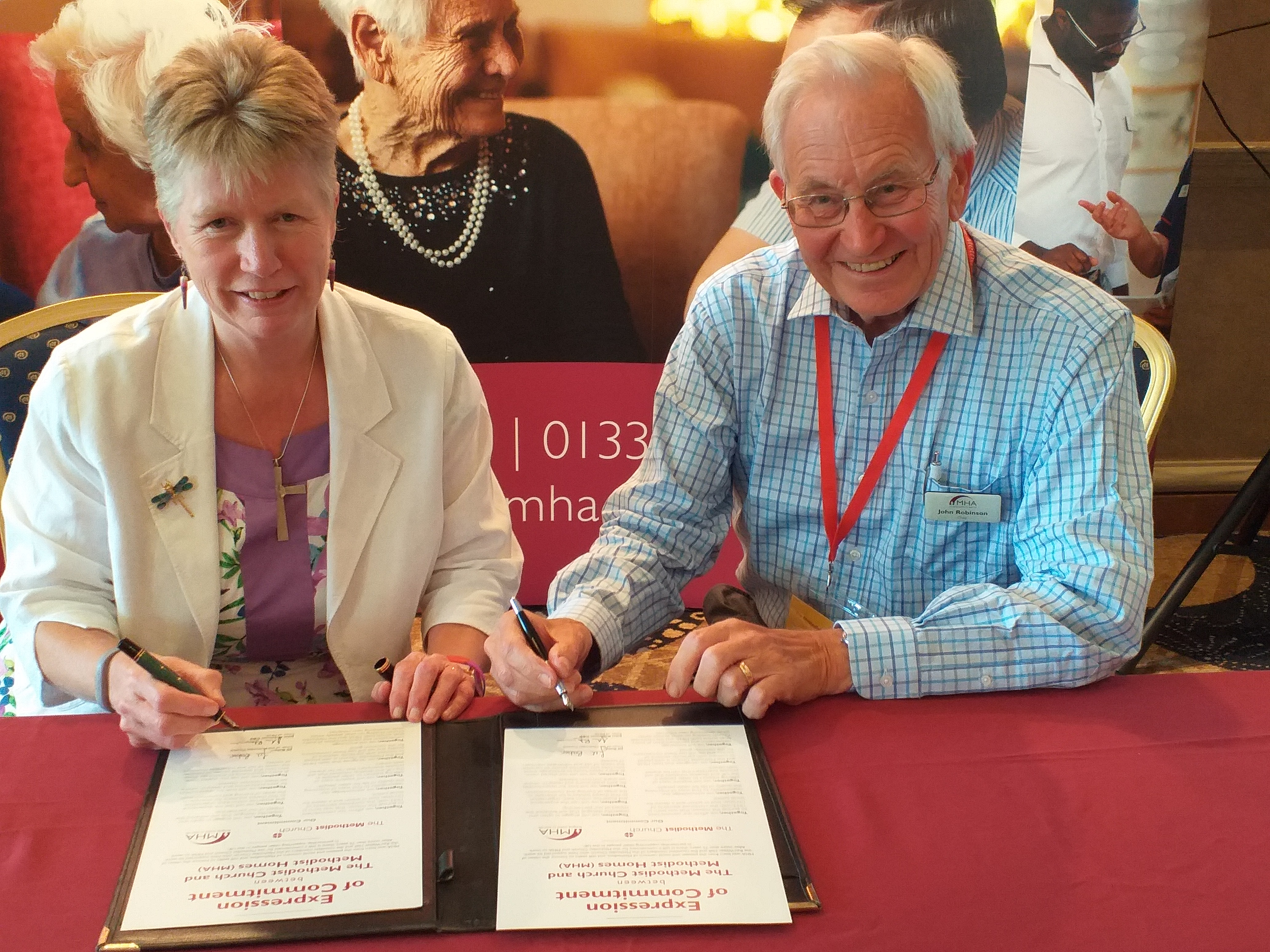 Jill Baker and John Robinson sign the Expression of Commitment